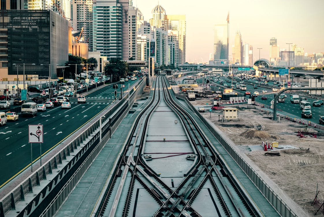 Tilt-shift Photography of Railway in Between of Roads at Day