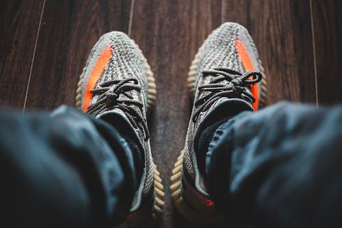 Crop person in sneakers on wooden floor