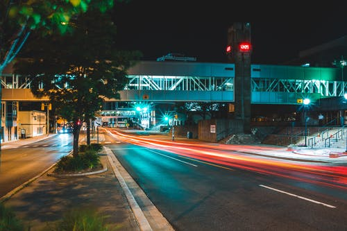 City road with pedestrian overpass at night