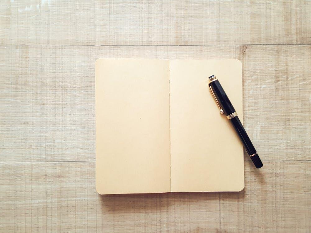 Black Twist Pen on Top of Open White Notebook