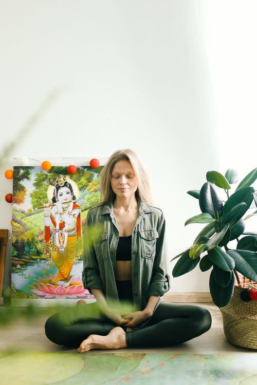 Woman in Black Leather Jacket Sitting Beside Green Plant