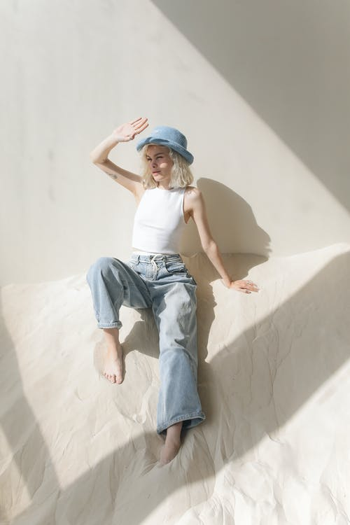Woman in White Top and Blue Denim Jeans