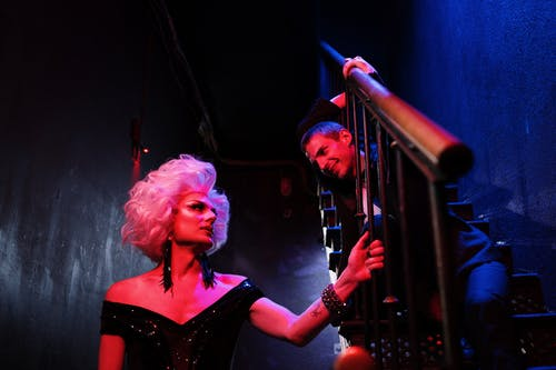 Man Sitting on Stairs Looking at a Drag Queen