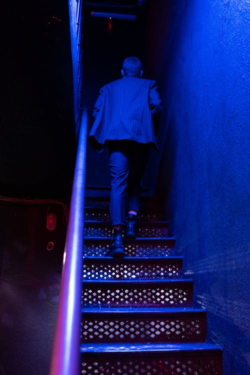 Man in Blue and White Plaid Dress Shirt and Black Pants Standing on Staircase