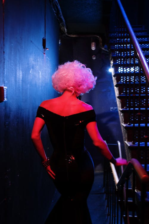 Drag Queen in Black Dress Going Down Stairs