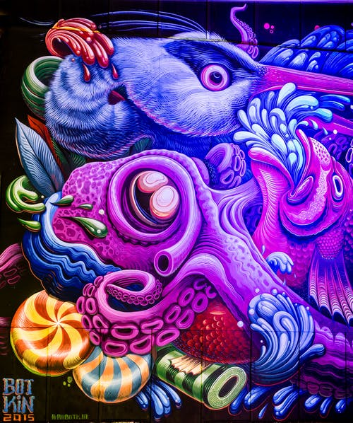Colorful illustration on graffiti wall representing fantastic fish and water flows  in daylight