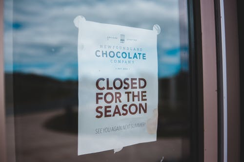 Announcement on white paper with CLOSED FOR THE SEASON inscription attached to glass surface at daytime
