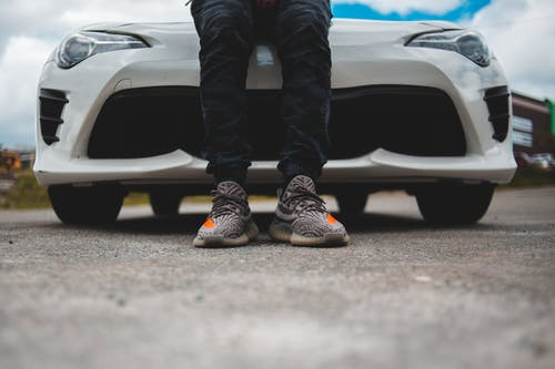 Person in Black Pants and Gray Sneakers Standing Beside White Car