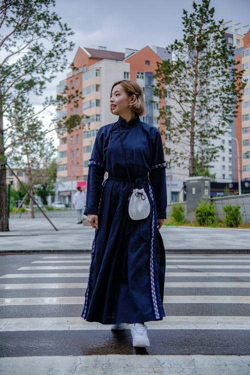 Woman in Blue Dress Walking on Pedestrian Lane