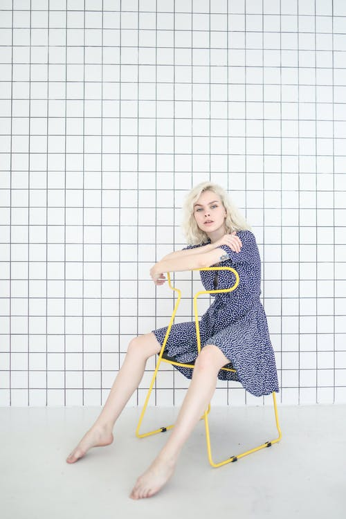 Photo of Girl in Blue Dress While Sitting on Chair
