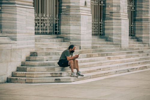 Man in Black T-shirt and Black Shorts Sitting on Concrete Stairs