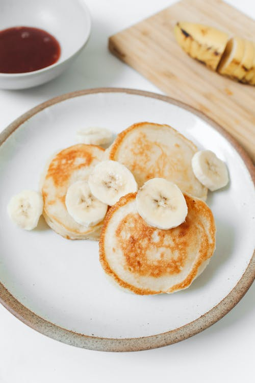 Photo of Pancakes With Banana on White Ceramic Plate