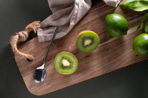 Sliced Green Apple Beside Silver Spoon on Brown Wooden Table