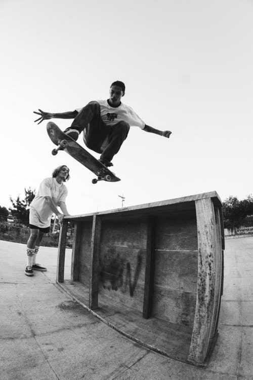 Young active skater leaping high in park