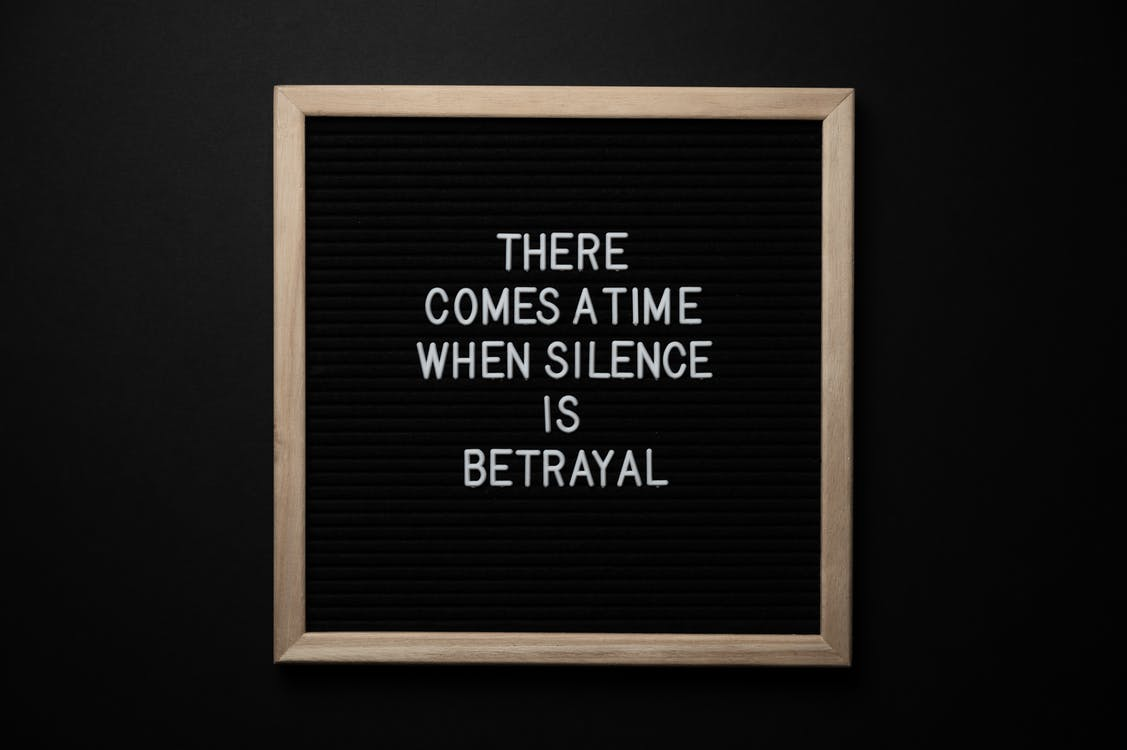 From above chalkboard with THERE COMES A TIME WHEN SILENCE IS BETRAYAL inscription on black background