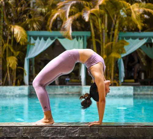 Woman in Pink Leggings and Black Sports Bra Doing Yoga Near Swimming Pool