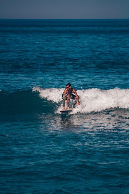 Fit man balancing on surfboard on rippling blue sea