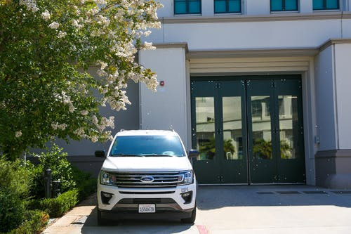 White automobile parked on pavement under blooming lilac next to wide doors of house in sunlight