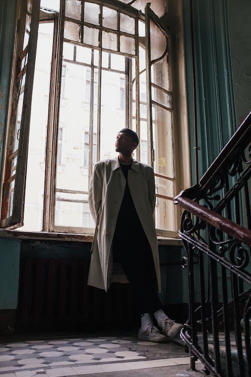 Man in White Coat Standing Near Window
