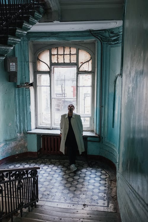 Man in White Robe Standing on Hallway