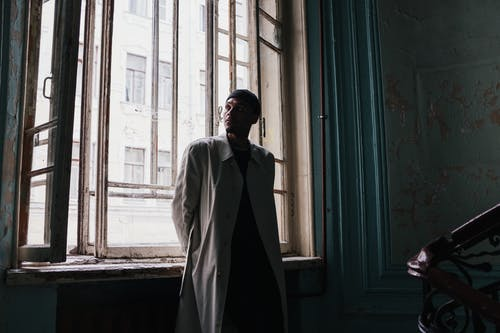 Man in White Coat Standing Beside Window