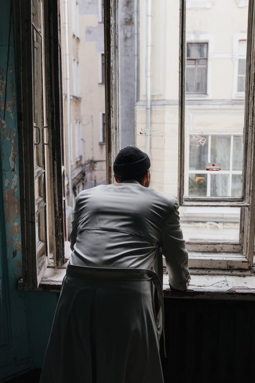 Man in Gray Long Sleeve Shirt and Black Pants Standing in Front of Window