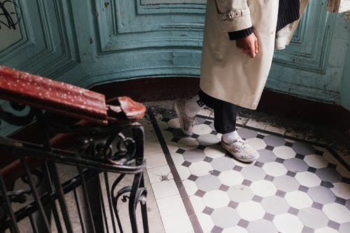 Person in White Coat Standing on White and Black Floor Tiles