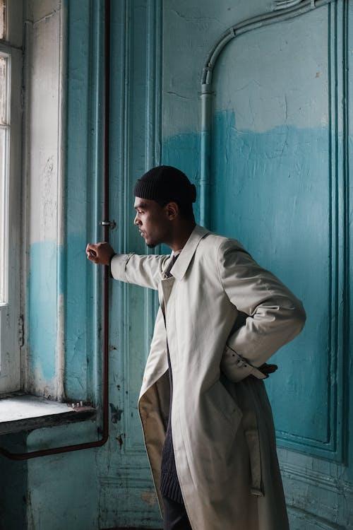 Man in Brown Coat Standing Beside Blue Wooden Door