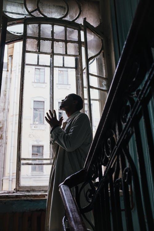Man in White Dress Shirt Standing Near Window