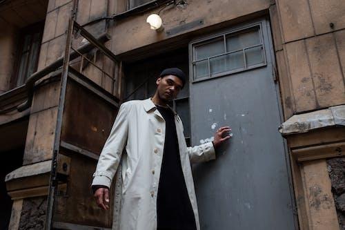 Man in White Coat Standing Beside Blue Wooden Door