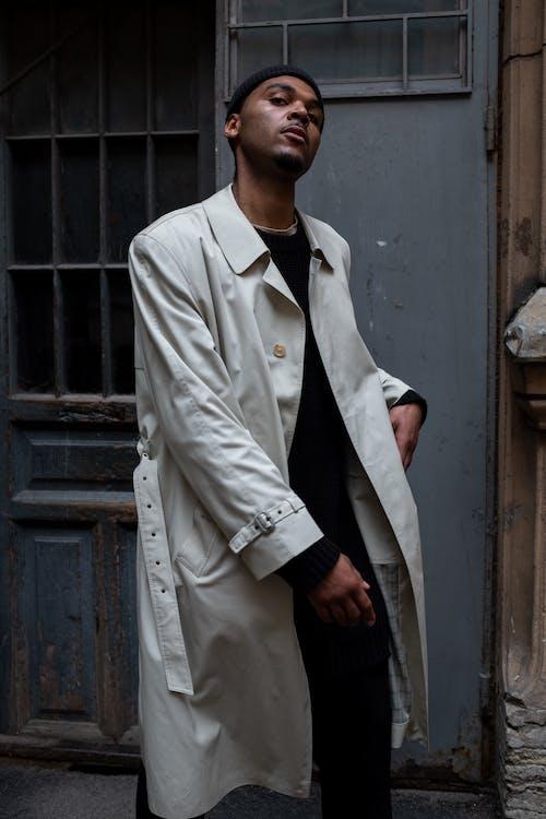 Man in White Coat Standing Beside Gray Wooden Door
