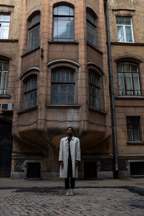 Man in White Thobe Standing Beside Brown Concrete Building