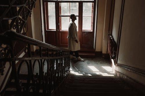 Man in Brown Coat Standing on Hallway