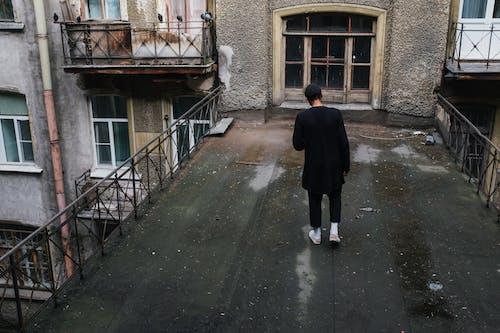 Man in Black Coat Walking on Sidewalk