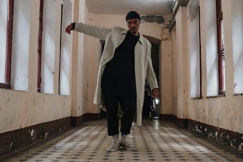 Man in Black Jacket and Black Pants Standing on Brown Wooden Floor