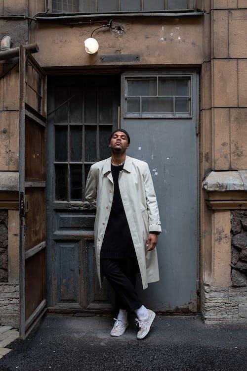Man in White Coat Standing Beside Brown Wooden Door