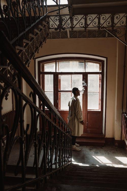 Man in White Dress Shirt Standing Near Brown Wooden Door