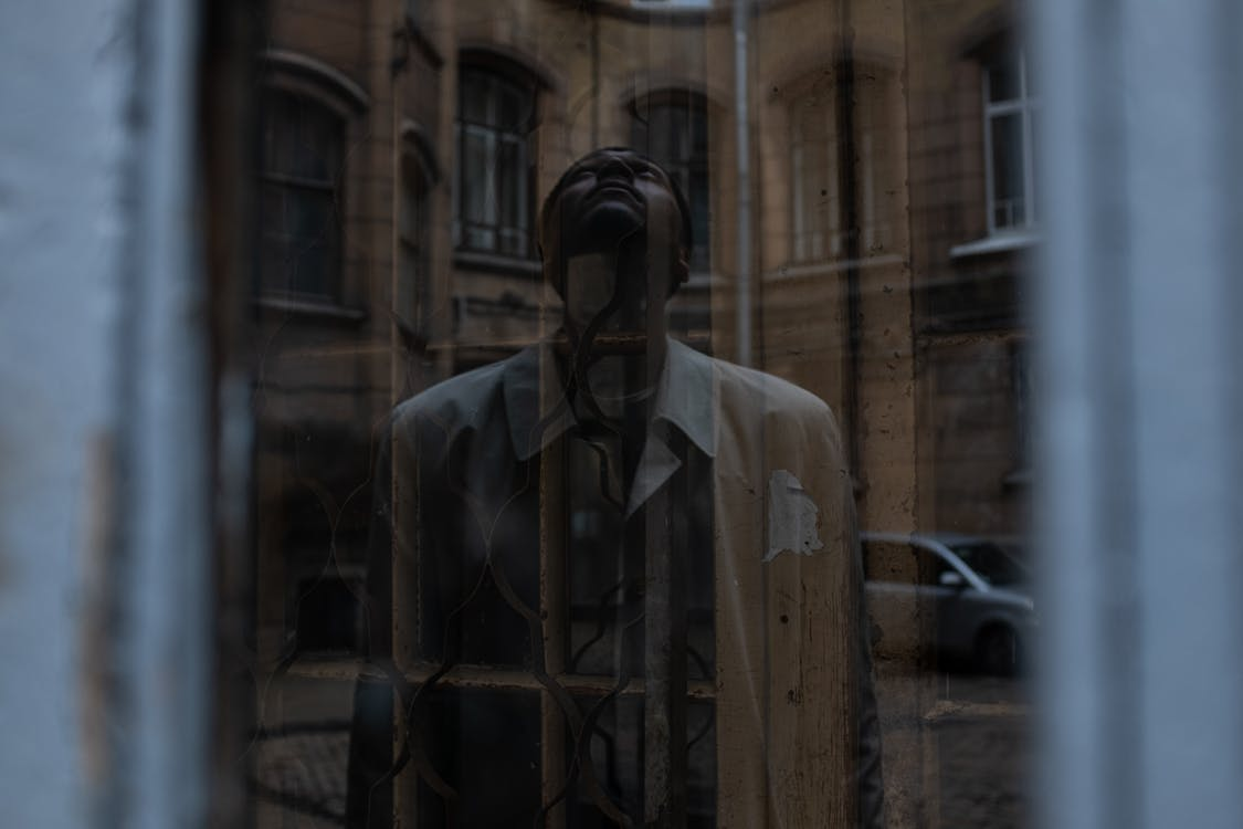 Man in White Button Up Shirt Standing Beside Brown Wooden Door
