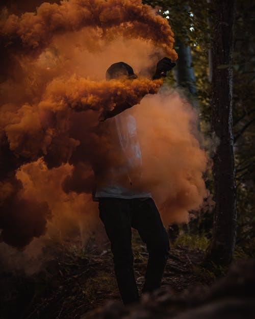 Man in Black Jacket Standing in Front of Orange Smoke