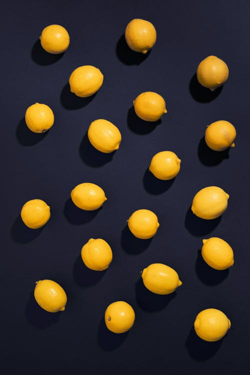 Желтые круглые фрукты на черной поверхности