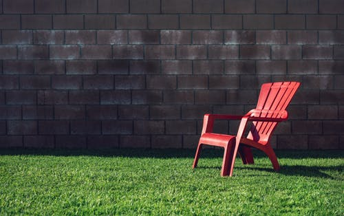 Red Plastic Armchair on Green Grass Field