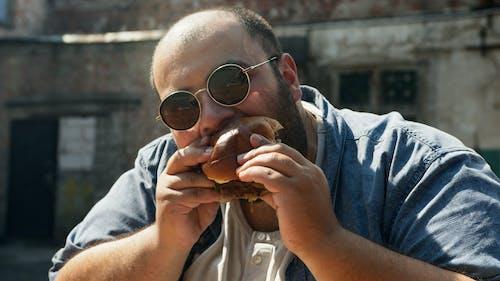 Man in Blue Denim Jacket Eating Bread