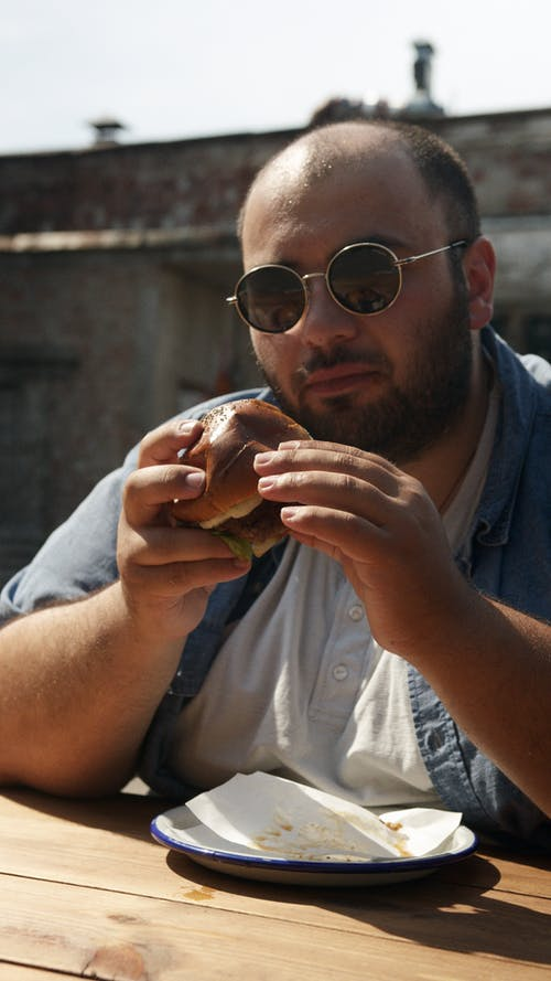Man in White Button Up Shirt Holding Bread