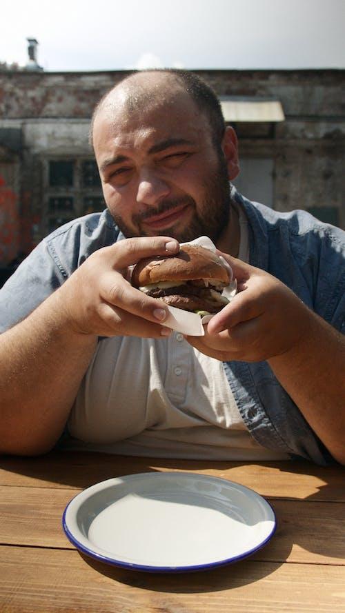 Man in Gray Shirt Holding Burger