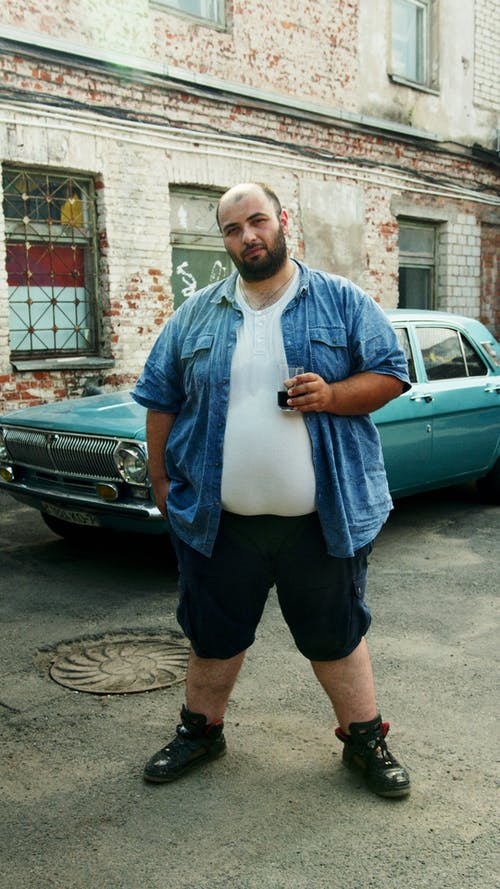 Man in Blue Button Up Shirt and Black Shorts Standing Beside Green Car