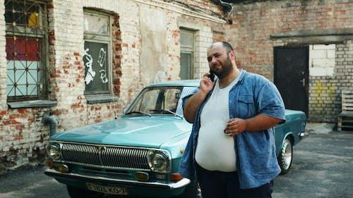 Man in Blue Dress Shirt Standing Beside Teal Car