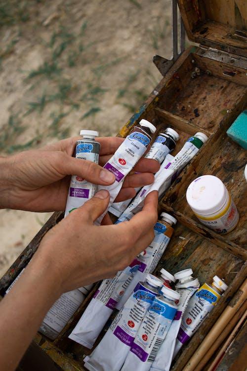 Crop female artist choosing oil paints in nature