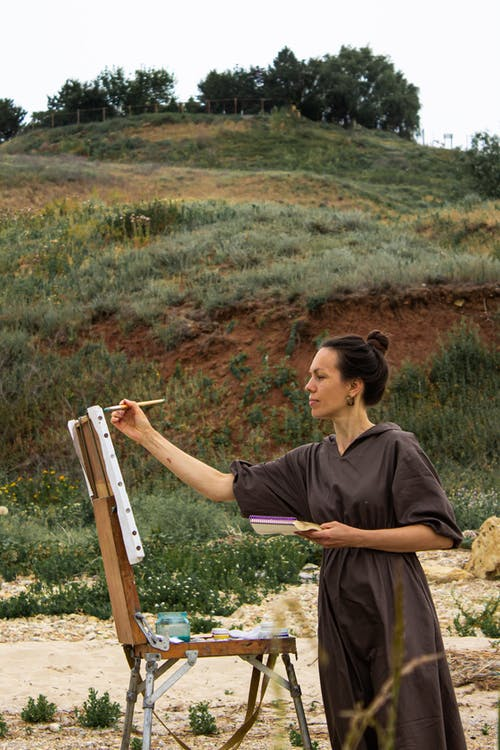 Side view of creative female painter standing on sandy ground and drawing picture of nature
