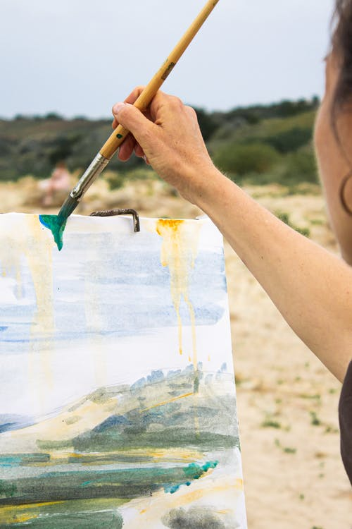 Artist with brush drawing nature on canvas