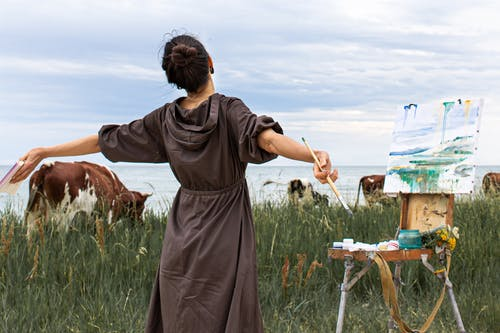 Young woman with arms outstretched painting nature